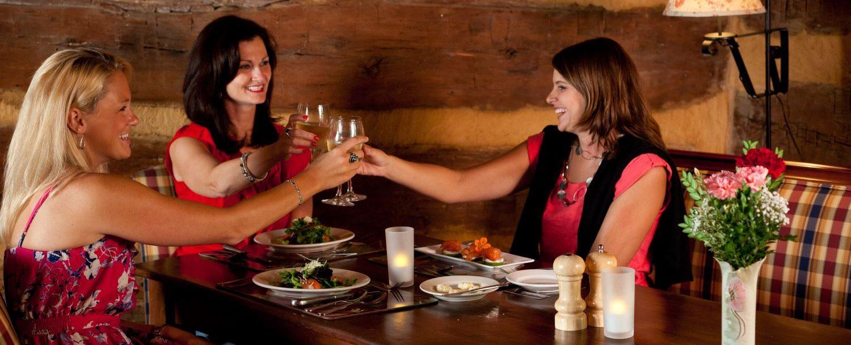 three women cheering wine glasses in a restaurant